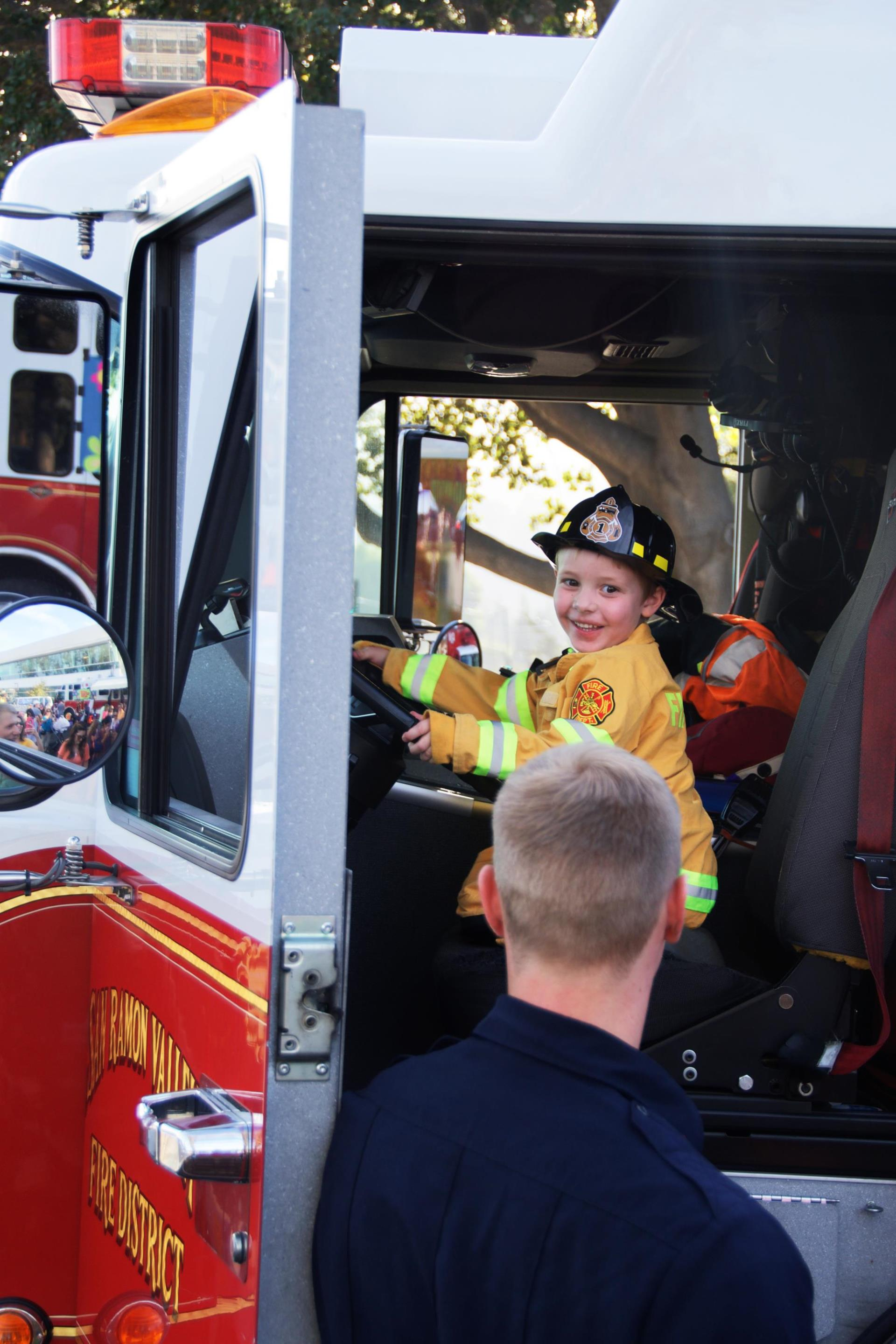 Kid dressed up as Firefighter in engine