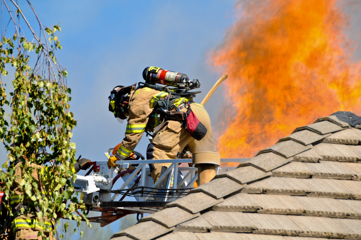 ladder on roof with flames