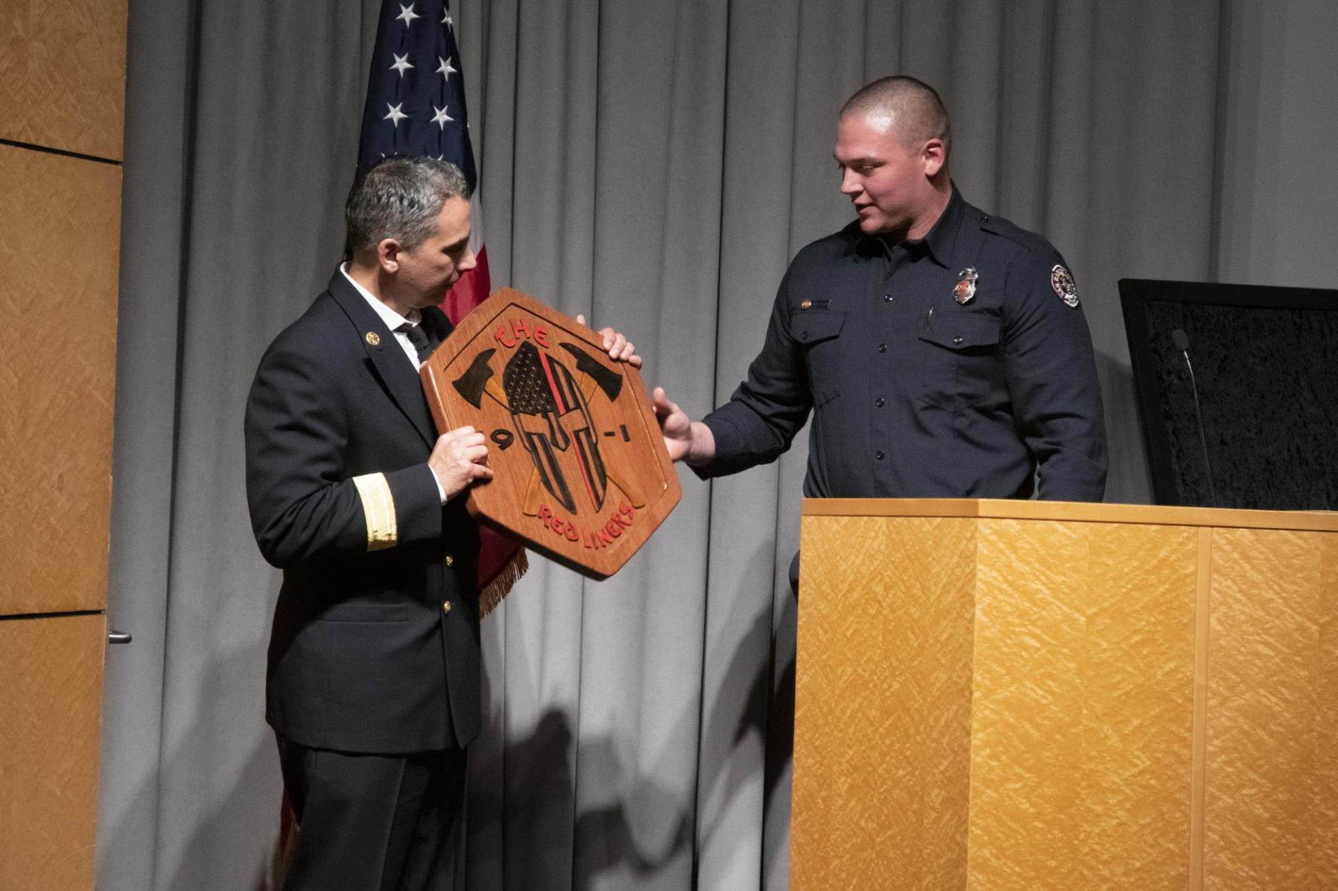Recruit Grant Dakin presenting Chief Meyer with hand carved academy logo