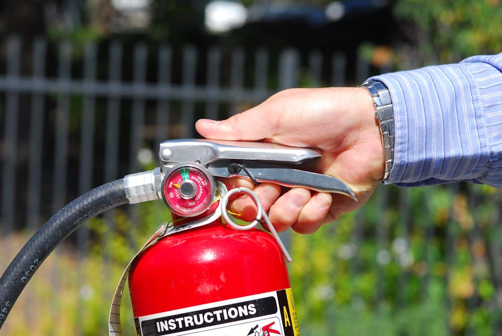 Squeeze the lever of fire extinguisher